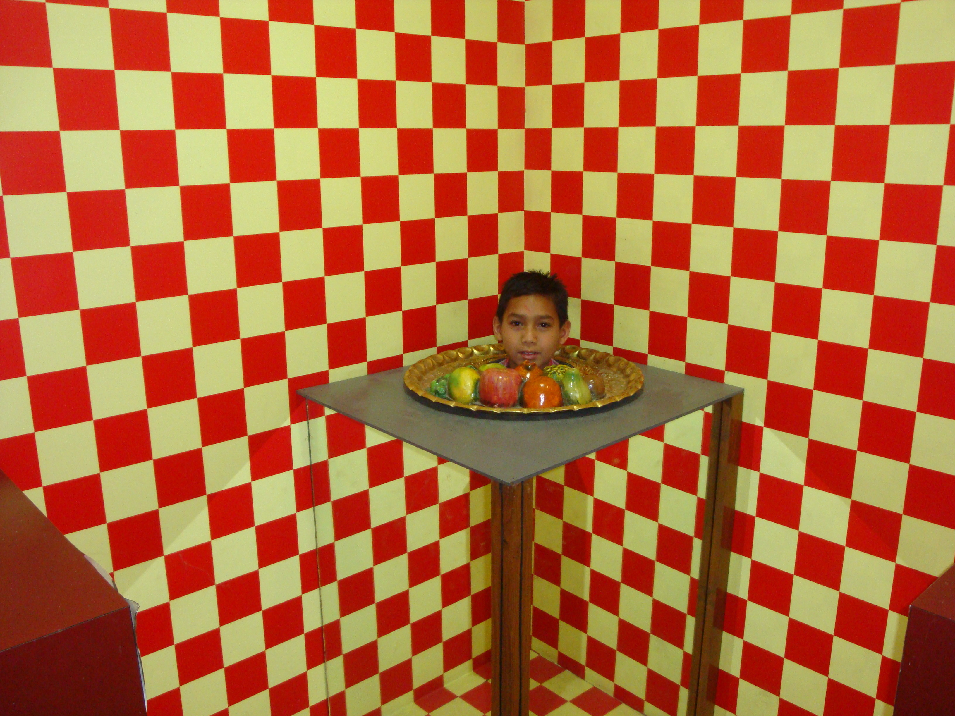 afbeelding van een illusie waarbij een hoofd van een kind op een fruitschaal lijkt te liggen. Gelukkig is dit allemaal een illusie.